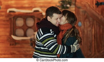 The girl and the boyfriend embrace and enjoy each other against the backdrop of a fairy-tale house. Christmas and New Year theme.
