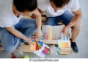 The girl and the guy to pick a color for painting walls