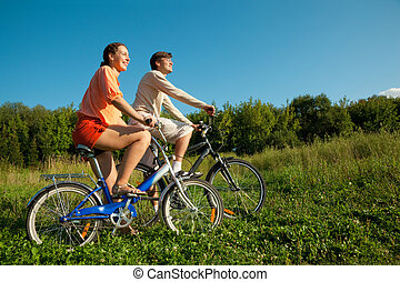 The girl and the man go for a drive on bicycles in a sunny day