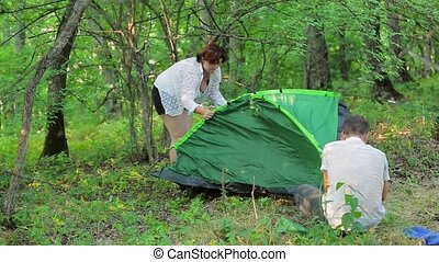 The girl and the man set the tent in the deciduous forest.