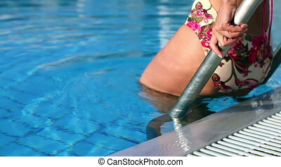 Girl falls into the pool with blue, clear water