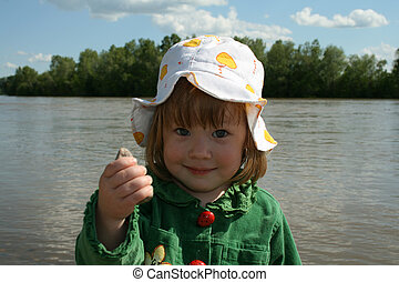 The girl ashore of river - Small girl in green plays ashore ...
