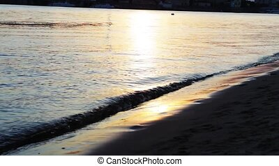 The girl at sunset walks barefoot along the shore. The girl walks barefoot on the water.