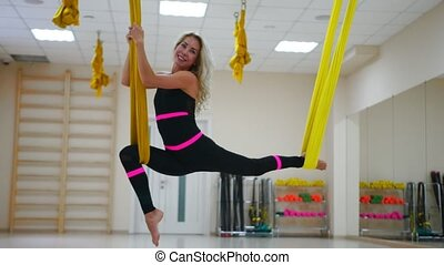 The girl at the Aero yoga classes is in the twine sitting on a hammock in the air