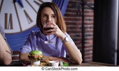 The girl at the restaurant is drinking wine. The brunette was brought her a hamburger, and she is ready to eat it. Very nice serving of dishes with snacks
