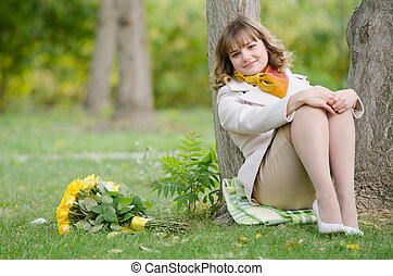 The girl at the tree with a bouquet of yellow roses