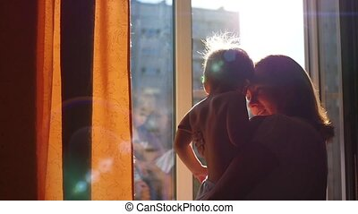 the girl at the window kissing a child in the sun