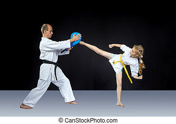 The girl beats a high kick leg on the simulator
