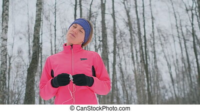 The girl before the morning winter jog inserts headphones in...