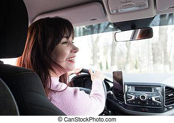Girl behind the wheel smiles