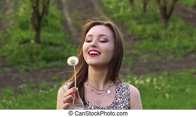 The girl blowing dandelion, looking aside and smiling . Slow motion