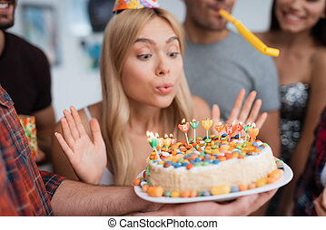 The girl blows out the candles on the birthday cake. A girl...