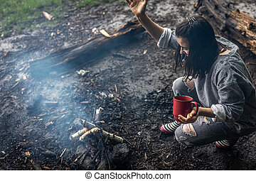 A girl with a cup in her hand is fanning the fire to keep warm.