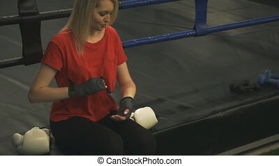 The girl boxer sits in the ring and straightens the bandages...