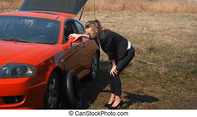 the girl broke the wheel and trying to change it in the...