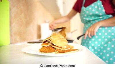 The girl chef removes the finished pancakes with a spatula from the pan. A mountain of pancakes in a plate in the foreground. High quality 4k footage