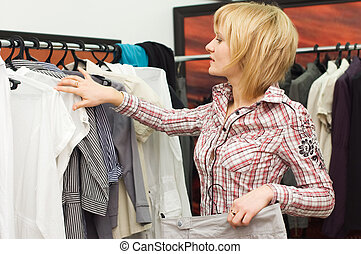 The girl chooses clothes in a boutique