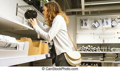 The girl chooses cookware in the shop, 4K. - The girl...