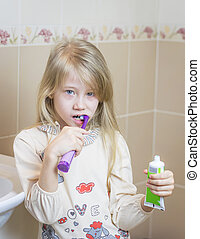 The girl cleans her teeth and holds a toothpaste in her hands.