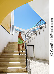 The girl climbs up the stairs in the southern resort town