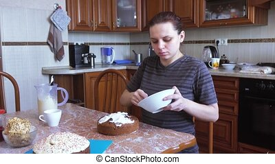 The girl covers the Easter cake with frosting - On the...