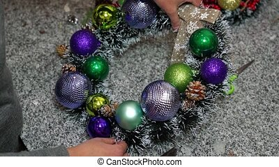 The girl creates a festive wreath for the New Year and ...