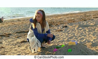 The girl creates a sand castle. - The girl makes a castle...