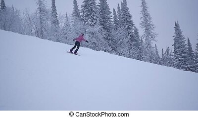 the girl descends from the mountain on snowboard in slowmo
