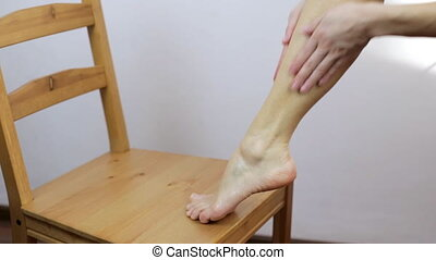 The girl does a foot massage after the depilation procedure....