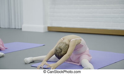 The girl does half split body bent during the ballet class...