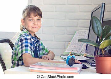 The girl does homework at the table, looked into the frame