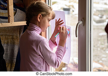 The girl draws a picture on a blank sheet by attaching the picture to the window glass