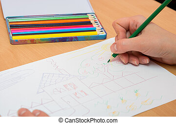 The girl draws a picture with colored pencils on paper, close-up