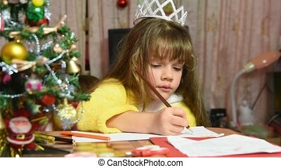 The girl draws at the table Christmas drawing