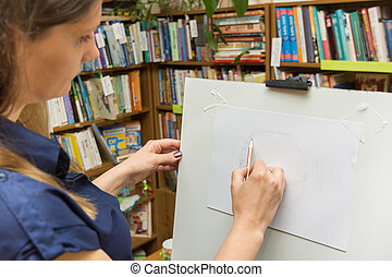 The girl draws on the easel in the library
