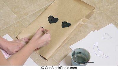 The girl draws with a brush on paper bags various emotions....