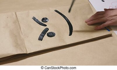 The girl draws with a brush on paper bags various emotions. The concept of emotions in smileys