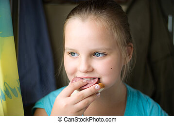 The girl eats a sandwich with sausage