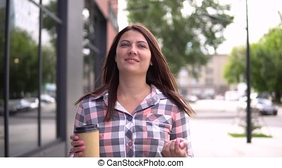 The girl goes after shopping with bags in her hands drinking coffee. 4K