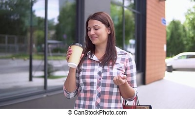 The girl goes after shopping with packages and holds a glass with coffee in her hand. slow motion. HD