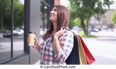 The girl goes after shopping with packages and holds a glass with coffee in her hand. slow motion.