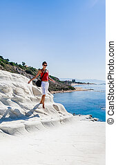 """The girl goes on a slope of white cliff called """"Scala dei Turchi"""" in Sicily, near Agrigento. Italy"""
