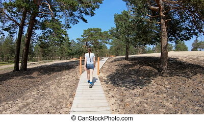The girl goes on a tourist forest path - Girl walking along...