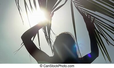 The girl goes through a branch of a palm tree to the sea resting on the beach and the sun shines through the palm tree with lens flare effects in slow motion. 1920x1080