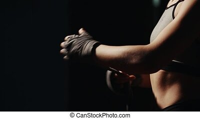 The girl herself bandaging his hands with bandages before the bout on a black background. Prepare for battle. close-up of hands. Mixed martial arts.