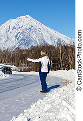 The girl hitchhiking on the winter road