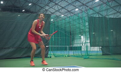 The girl hits the ball with a tennis racket and laughs