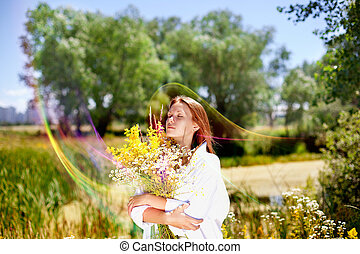 The girl holds a bouquet of wild flowers in hand.