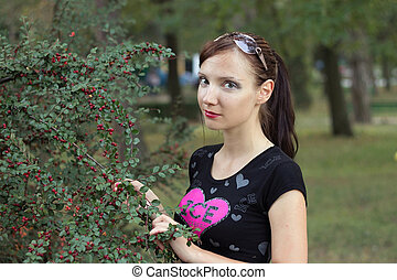 The girl holds a dogrose branch with red berries