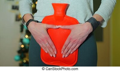 The girl holds a red heating pad in the abdomen to relieve symptoms of PMS. Hands tightly press the warm heating pad.